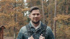 Portret van de Jonge Gebaarde Mens in Autumn Forest With een Toeristische Rugzak, Autumn Style, Reizende Levensstijl stock footage