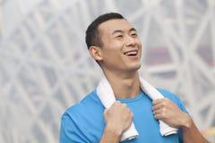 Portret van de jonge glimlachende atletische mens in een blauwe t-shirt in openlucht met handdoek rond hals Stock Foto's
