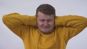 Portret van de jonge grappige Kaukasische mens die zijn oren sluiten alsof hij ongerust gemaakte bang is om slecht iets te vernem stock video