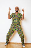 Portret van de jonge knappe Afrikaanse mens die het heldergroene nationale kostuum het glimlachen gesturing dragen Royalty-vrije Stock Afbeeldingen