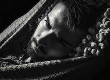 Portret van de jonge knappe ernstige mens in een hangmat stock afbeelding