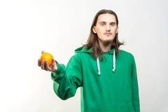 Portret van de jonge knappe geparelde mens in groene hoodie die een sinaasappel in zijn hand houden Royalty-vrije Stock Foto's
