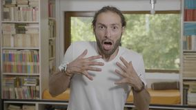 Portret van de jonge knappe mens die thuis het verraste geschokte en doen schrikken gillen en handen opheffen kijken - stock footage