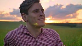 Portret van de jonge knappe vooruit en mens die, mooi landschap met zonsondergang op achtergrond kijken glimlachen stock videobeelden