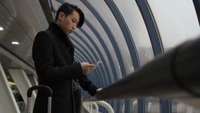 Portret van de jonge Koreaanse mens die zich in de luchthaven bevindt en messege typt stock videobeelden