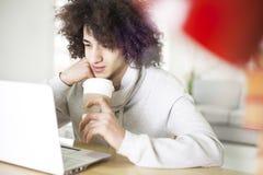 Portret van de jonge mens die computer met behulp van Stock Afbeelding