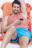Portret van de jonge mens die met telefoon in de handen glimlachen stock afbeelding