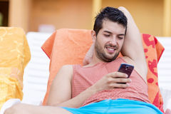 Portret van de jonge mens die met telefoon in de handen lachen stock afbeelding
