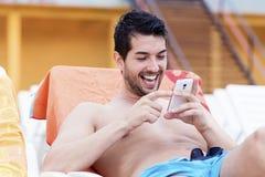 Portret van de jonge mens die met telefoon in de handen lachen stock fotografie