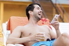Portret van de jonge mens die met telefoon in de handen lachen royalty-vrije stock afbeeldingen