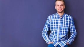 Portret van de jonge mens die op grijze achtergrond glimlachen Stock Foto