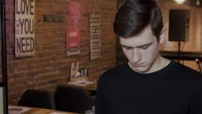 Portret van de jonge mens, die zich in modieuze koffie bevindt stock videobeelden