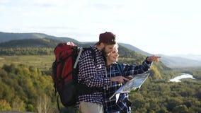 Portret van de jonge mens en vrouw met kaart in de bergen wordt geschoten die stock footage