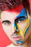 Portret van de jonge mens met gekleurde gezichtsverf op rode achtergrond Professionele Make-upmanier De make-up van de fantasieku Stock Foto