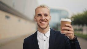 Portret van de jonge mens met koffie die de camera onderzoeken Het lachen vrolijk portret van de succesvolle bedrijfsmens stock video