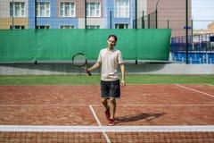 Portret van de jonge mens op de schooltennisbaan van de de zomercampus stock fotografie