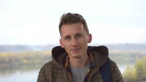 Portret van de jonge mens in openlucht met zeer knap gezicht in toevallig jasje en overhemd tegen natuurlijke achtergrond stock videobeelden