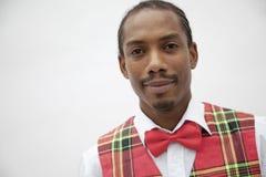 Portret van de jonge mens in plaidvest en rode vlinderdas, studioschot Royalty-vrije Stock Foto