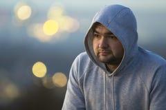 Portret van de jonge mens in sweatshirt met een kap/verbindingsdraad op vage B stock fotografie