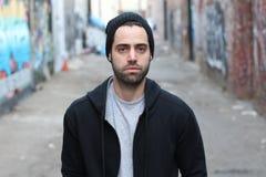Portret van de jonge mens tegen lege stedelijke steegmanier - Voorraadbeeld royalty-vrije stock afbeelding
