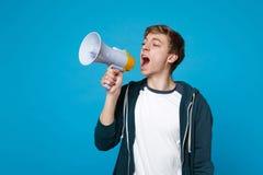 Portret van de jonge mens in vrijetijdskleding die, schreeuw op megafoon opzij eruit zien die op blauwe muurachtergrond wordt geï royalty-vrije stock fotografie