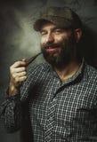 Portret van de jonge modieuze mens met een baard met een pijp Stock Afbeeldingen