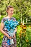 Portret van de jonge mooie glimlachende vrouw met lange haar en bloemen in openlucht Stock Foto