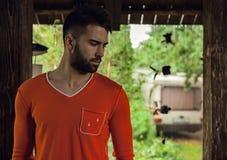 Portret van de jonge mooie mens in sinaasappel, tegen openluchtachtergrond Royalty-vrije Stock Foto's