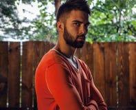 Portret van de jonge mooie mens in sinaasappel, tegen openluchtachtergrond Stock Afbeeldingen