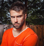 Portret van de jonge mooie mens in sinaasappel, tegen openluchtachtergrond Stock Foto's