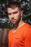 Portret van de jonge mooie mens in sinaasappel, tegen openluchtachtergrond Royalty-vrije Stock Afbeelding