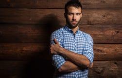 Portret van de jonge mooie modieuze mens tegen houten muur stock foto