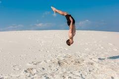 Portret van de jonge parkourmens die tik of salto mortale op het zand doen stock foto's