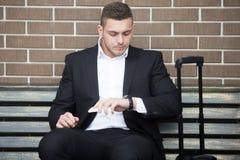 Portret van de jonge reizende mens die tijd controleren stock foto