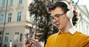 Portret van de jonge tienerkerel in hoofdtelefoons en oogglazen die en via de mobiele telefoon babbelen doorbladeren terwijl het  stock footage