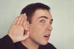 Portret van de jonge toevallige mens dat gesprek afluistert concept doofheid of het afluisteren Hard van Hoorzitting stock afbeeldingen