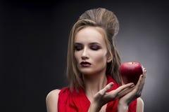 Portret van de jonge vrouw in een rode sjaal met een voorhoedekapsel dat in hand rode appel op een grijze achtergrond houdt Royalty-vrije Stock Afbeeldingen