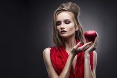 Portret van de jonge vrouw in een rode sjaal met een voorhoedekapsel dat in hand rode appel op een grijze achtergrond houdt Stock Afbeeldingen