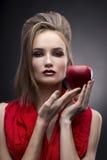Portret van de jonge vrouw in een rode sjaal met een voorhoedekapsel dat in hand rode appel op een grijze achtergrond houdt Royalty-vrije Stock Foto