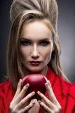 Portret van de jonge vrouw in een rode sjaal met een voorhoedekapsel dat in hand rode appel op een grijze achtergrond houdt Royalty-vrije Stock Fotografie