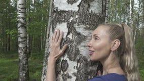 Portret van de jonge vrouw met een lang eerlijk haar van de berk die een boomstam in het berkehout omhelzen stock videobeelden