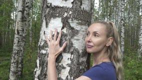 Portret van de jonge vrouw met een lang eerlijk haar van de berk die een boomstam in het berkehout omhelzen stock footage