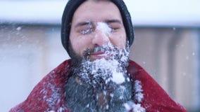 Portret van de kalme gebaarde mens die close-up in camera kijken Grote sneeuwbalvliegen en neerstortingen op het gezicht van een  stock videobeelden