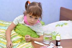 Portret van de kleine zieke meisjeszitting in een bed dichtbij drugs Stock Foto