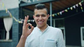 Portret van de knappe Arabische mens die O.K. gebaar tonen en outoors in stad glimlachen stock videobeelden