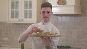 Portret van de knappe glimlachende jonge mens die houten plaat met dicht omhoog pizza houden Concept voedselvoorbereiding stock video