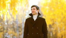 Portret van de knappe glimlachende mens die een zwart laagjasje in de zonnige herfst dragen stock afbeelding