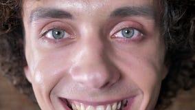 Portret van de knappe jonge glimlachende mens die camera, krullend haar en blauwe ogen bekijken stock footage