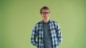 Portret van de knappe jonge mens die camera bekijken en op groene achtergrond knipogen stock videobeelden