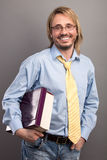 Portret van de knappe jonge mens die een omslag en een boek houden royalty-vrije stock foto's